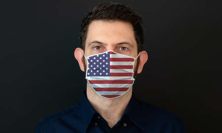 Man wearing American flag protective medical face mask. He looks worried and concerned. concept in United States of America with black background.