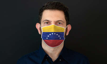 Man wearing Venezuelan flag protective medical face mask. He looks worried and concerned. concept in Venezuela with black background.