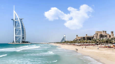 Dubai, UAE - May 31, 2013 The Burj Al Arab hotel on a sunny day with people in the shore. Publikacyjne