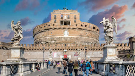 Rome, Italy February 2015: Tourists walking around Saint Angel Castle and bridge over the Tiber river under dramatic clouds