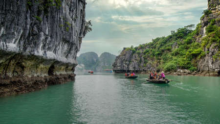 Halong Bay, Vietnam - December 2015: Tourists sailing in small boats in Halong Bay. Halong bay is a famous destination of Vietnam Publikacyjne