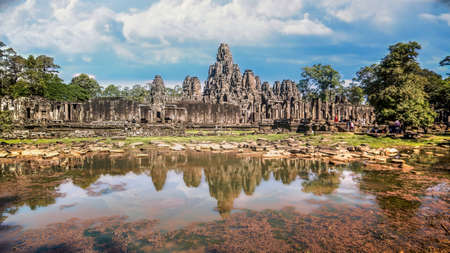 Siem Reap, Cambodia - December 2015: The many face temple of Bayon at the Angkor Wat site in Cambodia under dramatic clouds