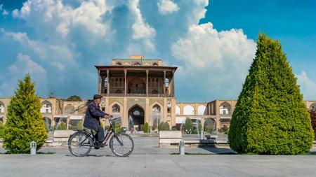 Isfahan, Iran - May 2019: Iranian man riding a bicycle with Ali Qapu Palace in Isfahan. Ali Qapu palace is located inside Naqsh-e Jahan Square in Isfahan