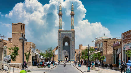 Yazd, Iran - May 2019: Local people and tourists around the gate and minarets of Jameh Mosque of Yazd