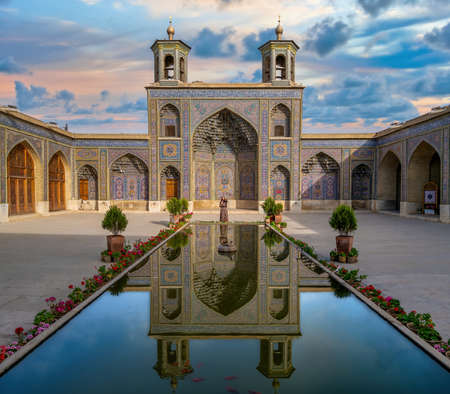 Shiraz, Iran - May 2019: Iranian woman standing by the pool of Nasir al-Mulk Mosque during sunset. Nasir Al-Mulk Mosque is also known as Pink Mosque. Publikacyjne