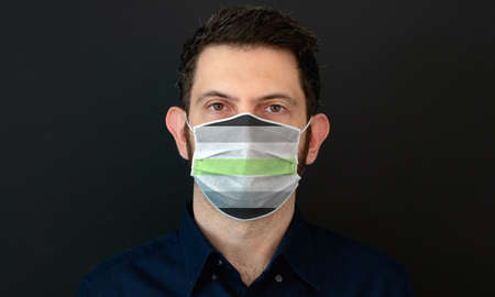 Portrait of an adult man wearing a LGBT agender flag colors facial mask. LGBT gay rights concept with black background. These colors symbolize the agender flag.
