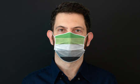Portrait of an adult man wearing a LGBT aromantic flag colors facial mask. LGBT gay rights concept with black background. These colors symbolize the aromantic flag.