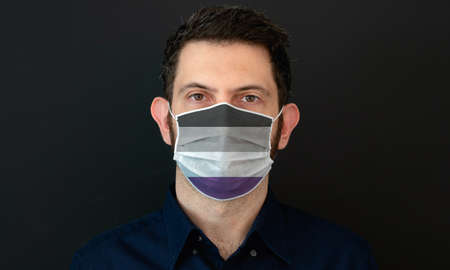 Portrait of an adult man wearing a LGBT asexual flag colors facial mask. LGBT gay rights concept with black background. These colors symbolize the asexual flag.