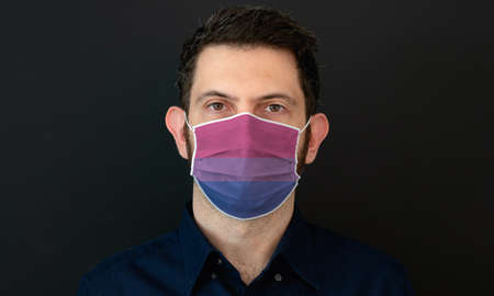 Portrait of an adult man wearing aLGBT bisexual flag colors facial mask. LGBT gay rights concept with black background. These colors symbolize bisexual flag.