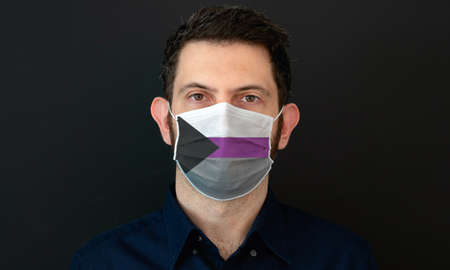 Portrait of an adult man wearing a LGBT demisexual flag colors facial mask. LGBT gay rights concept with black background. These colors symbolize the demisexual flag.