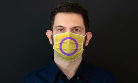 Portrait of an adult man wearing a LGBT intersex flag colors facial mask. LGBT gay rights concept with black background. These colors symbolize the intersex flag.