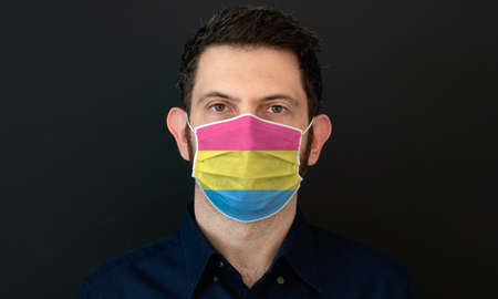 Portrait of an adult man wearing a LGBT pansexual flag colors facial mask. LGBT gay rights concept with black background. These colors symbolize the pansexual flag.