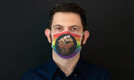 Portrait of an adult man wearing a LGBT Queer People of Color flag colors facial mask. LGBT gay rights concept with black background. Zdjęcie Seryjne