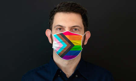Portrait of an adult man wearing a LGBT progress pride flag colors facial mask. New LGBT rainbow pride flag, LGBT gay rights concept with black background.