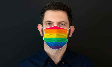 Portrait of an adult man wearing a LGBT rainbow pride flag colors facial mask. LGBT gay rights concept with black background.