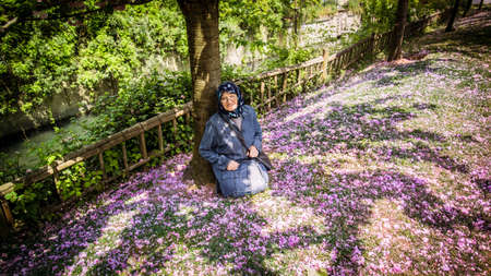Senior Muslim woman in a public park sitting under a tree over a bed of flowers. She looks happy and smiling looking at the camera