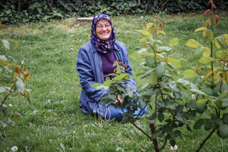 Senior Muslim woman in a public park sitting over grass by rose plants. She is laughing and very happy. Concept of happy muslim senior woman