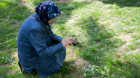 Senior Muslim woman with a camera taking a photograph of flower in the meadow. Concept of senior woman using a high-end camera and technology