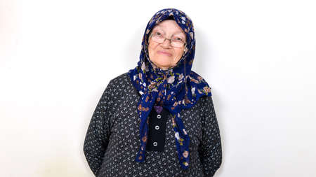 Senior Muslim woman looking at the camera and smiling over a white background. She is happy and joyful. Zdjęcie Seryjne