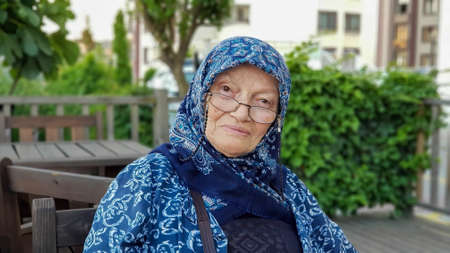 Senior Muslim woman looking at the camera and smiling. She is happy and smiling.