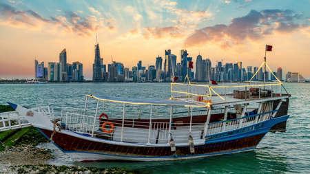Doha, Qatar - February 2019: Doha Qatar skyline with traditional Qatari Dhow boat in the harbor