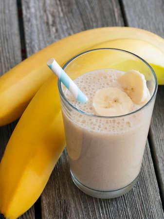 Banana Smoothie mit Bananenscheiben und Stroh Standard-Bild - 38914807