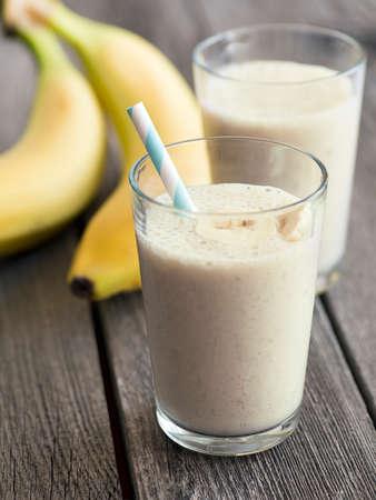 licuado de platano: Batido de plátano en un vaso sobre fondo de madera rústica Foto de archivo