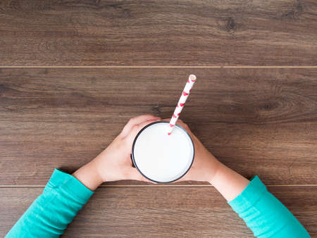 Child holding a glass of milk on wooden background Stock Photo