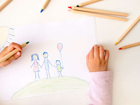 Child drawing a happy family