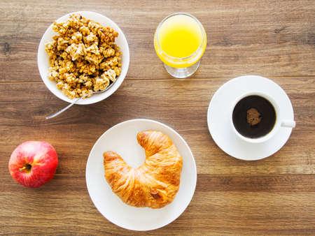 Frühstückstisch mit Apfel, Müsli, Saft, Croissant und Kaffee Standard-Bild - 88786644