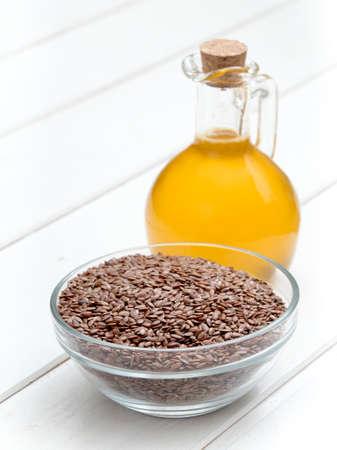 Leinöl in einer Flasche auf weißem Holzuntergrund Standard-Bild - 95769142