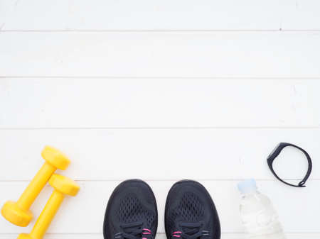 Sports equipment on white background. Running shoes, water, smart band and dumbbells top view with empty text space Standard-Bild - 105978229