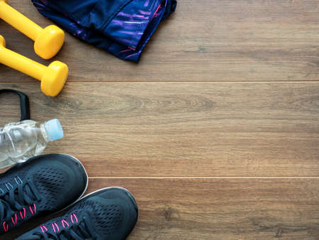 Healthy lifestyle concept background with running shoes, water, dumbbells, smart band and clothes on wooden background Standard-Bild - 105978232