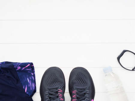 Running equipment on white wooden background. Running shoes, water, fitness band and running clothes top view Standard-Bild - 105978235