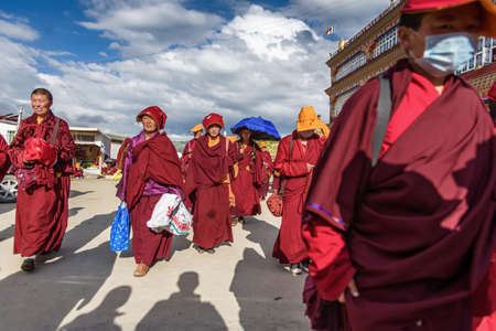 tantra: At Yaqing buddha college,Female lamas hurry to the buddhist ritual place. Editorial