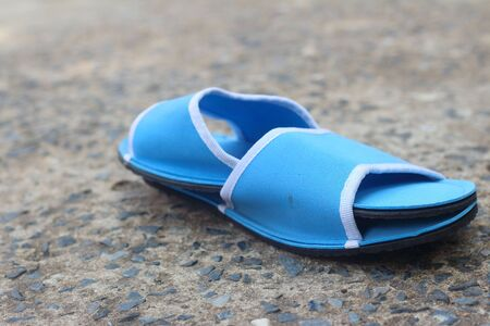 houseshoe: Slippers blue on a background of cement.