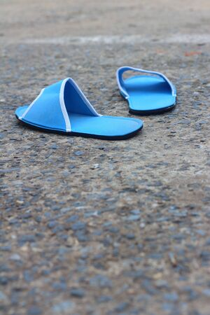 footgear: Slippers blue on a background of cement.