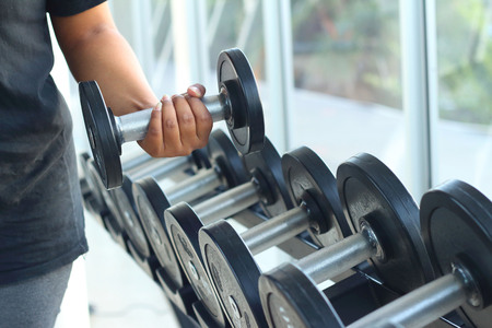 strong women: strong women hand takes a heavy dumbbell in gym Stock Photo