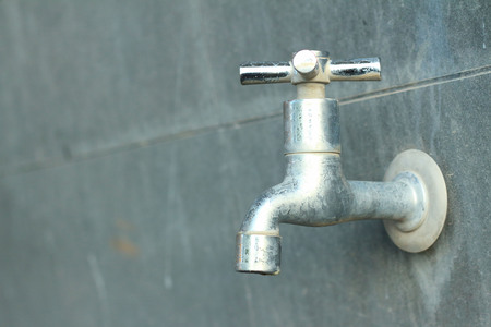cleansed: faucet on a gray background at the toilet