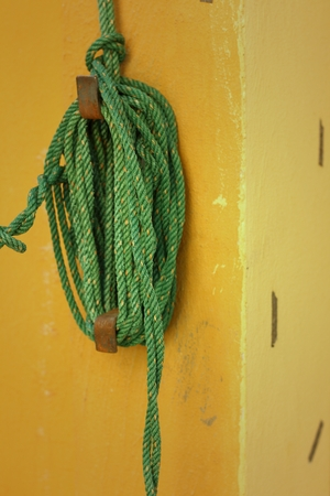 bollard: Green rope was tied to a pole.