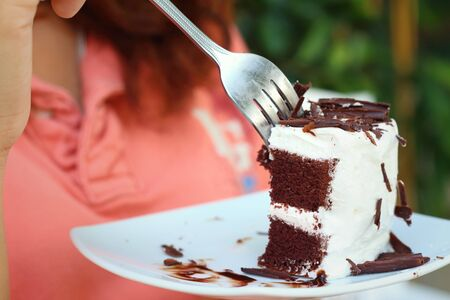 guilty pleasures: Woman eating chocolate cake at a cafe.