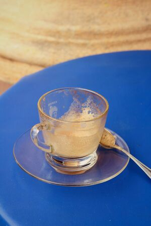 then: Coffee glass is then used on a blue background. Stock Photo