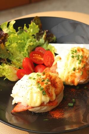 uk cuisine: Eggs Benedict ,vegetable ,eggs on a black plate. Stock Photo