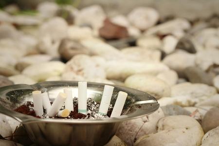 ashtray: Cigarette with ashtray on a stone background