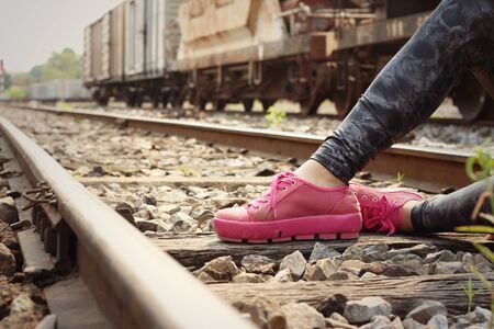 pink shoes: Woman wearing pink shoes at train station.