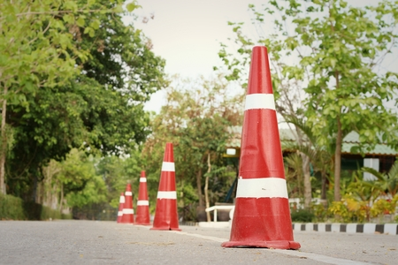 orange sign: orange traffic cones on the road at the park. Stock Photo