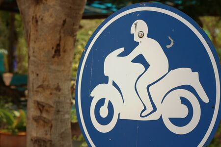disclose: Sign displaying the international symbol for a motorcycle
