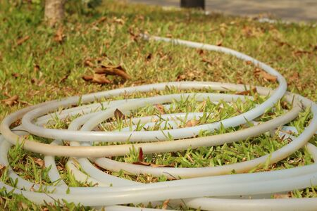 plastic conduit: rubber tube for watering plants on green grass.
