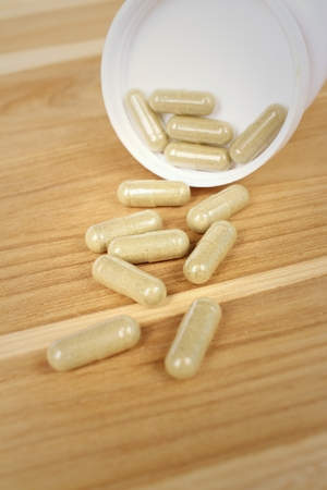 antibiotic pink pill: Medical pill on background of  wooden table.