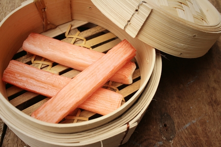 tast: Crab stick in bowl on brown background Stock Photo